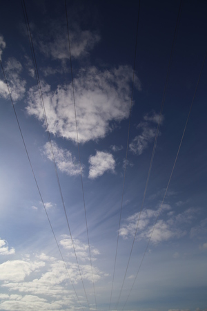 personal perspective: Cables on high voltage power line on a dark blue sky with cloudscape. Stock Photo