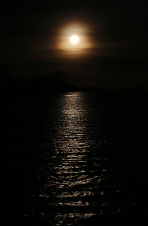 image created 21st century: Dark high contrast shot of misty sun with reflections on the water.