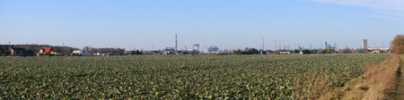 image date: Panoramic view over field to industrialharbor district of Rostock, Mecklenburg-Vorpommern, Germany.