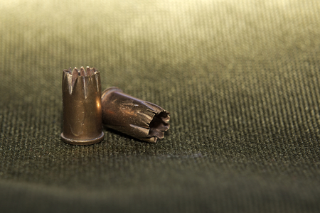 casings: Bullet casings on green textile with selective focus and unusual lighting.