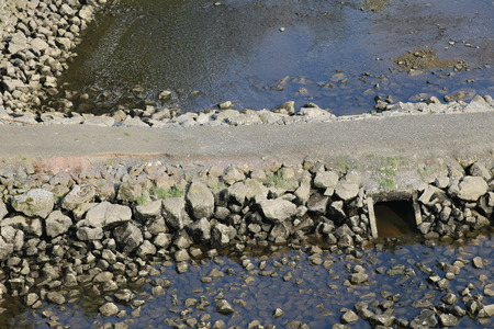 image created 21st century: A rock dam with sewer for the water on both sides. Stock Photo