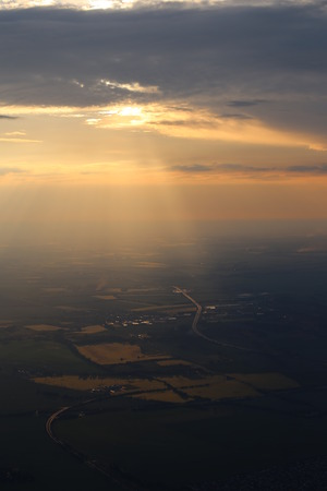 image created 21st century: View of the German city Magdeburg from a hot air balloon, orange sunbeams are breaking through the clouds. Stock Photo