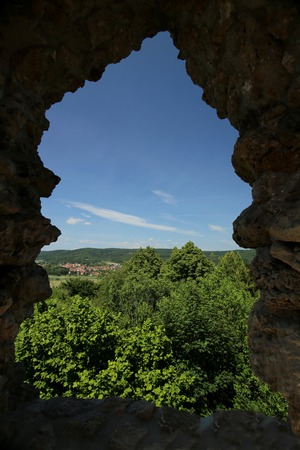 building feature: View through a small window on castle ruin Brandenburg. Some trees and a part of Herleshausen in Hesse, Germany, can be seen. Stock Photo