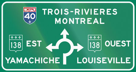 est: Guide and information road sign in Quebec, Canada - Roundabout with directions. Ouest means west, est means east.