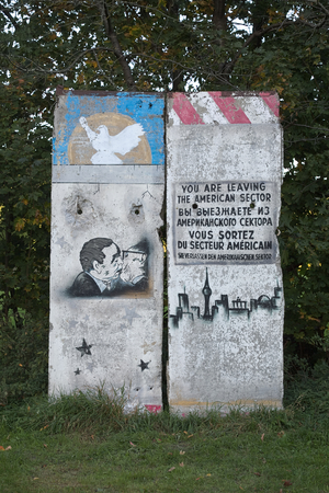 fraternal: GREIFSWALD, GERMANY - OCTOBER 10 2015: A part of the former Berlin Wall with historic graffiti paintings. The left painting depicts the socialist fraternal kiss of Brezhnev and Honecker.. Editorial