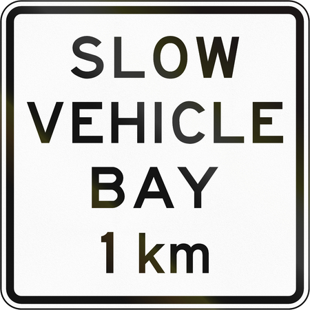 slow: New Zealand road sign - Slow vehicle bay ahead in 1 kilometre. Stock Photo