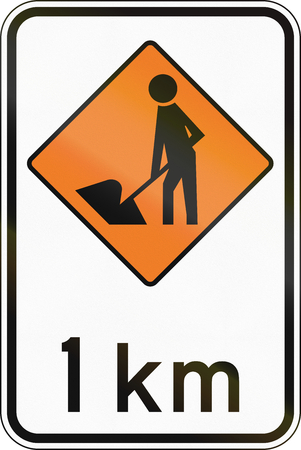 kilometre: New Zealand road sign - Road workers ahead in 1 kilometre.