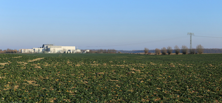 greifswald: Panoramic view over field with power lines and Max-Planck-Institute for plasma physics in Greifswald, Germany.