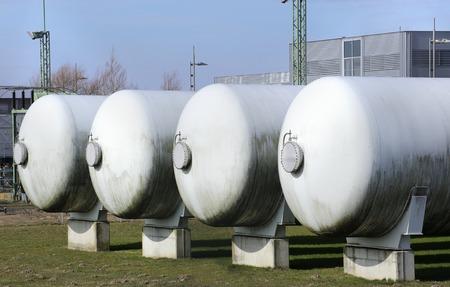 Quatre réservoirs de gaz industriels dans une rangée.