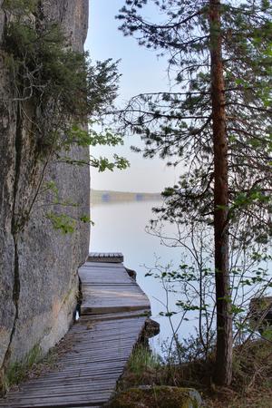 rock cliff: Wooden bridge leading around rock cliff at Faangsjoen in Sweden. Stock Photo