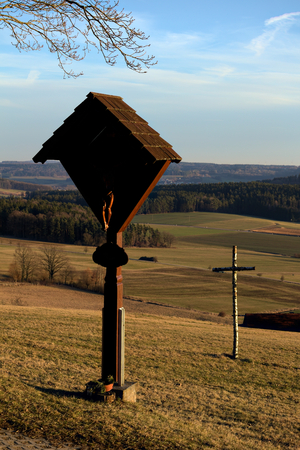 Wayside cross with carvings in shadow and a simple Birch cross. Stock Photo