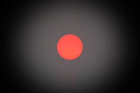 Faint red sun behind a dust cover, only seen as a red ball. Stock Photo