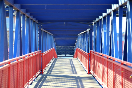 Passage through a steel bridge with red and blue parts. 스톡 콘텐츠 - 97702466