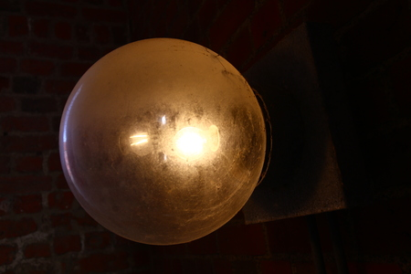Old globe lamp made of glass with dark background.