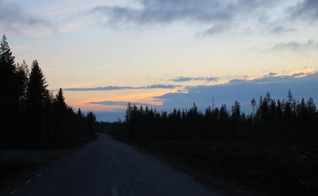 Jasny kolorowy zachód słońca i ciemny krajobraz w północnej Szwecji. Zdjęcie Seryjne