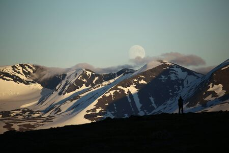 Clouds creeping over mountains in Abisko National Park in Sweden, with silhouette of unknown photographer.