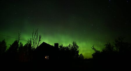 Northern lights over house in the night. Stok Fotoğraf