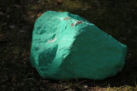Conceptual shot of a stone painted in turquoise.