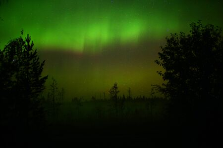 Northern lights over oncoming fog in the night.