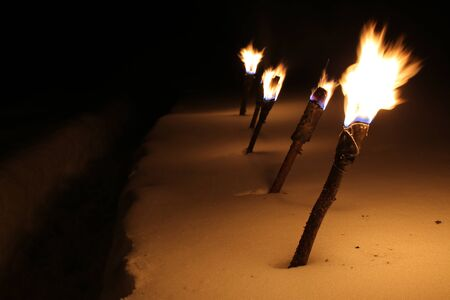 Row of burning torches in the snow.