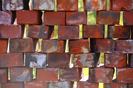 Stacked used bricks in front of blurred background. Stock fotó