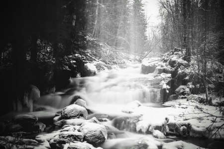 Moody long exposure shot of cascades in the small river Jaran in Bispgarden, Sweden. Light beams are coming from above. Stock Photo
