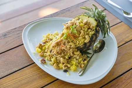 Fried rice in pineapple Thai style in white plate with spoon on the wooden table. Selective focus.