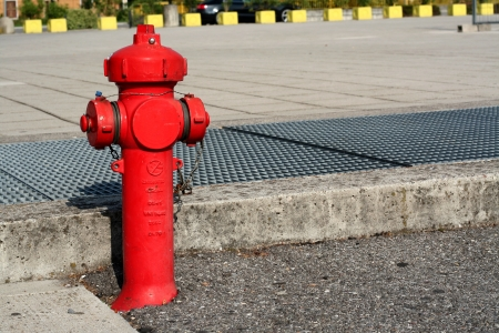 A red fire extinguisher in the street