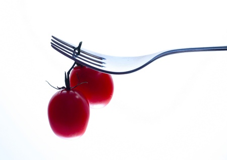Fork and two tomatoes isolated by white background Stock Photo