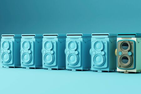 Colorful vintage camera surrounding by blue vintage camera on a blue background. 스톡 콘텐츠