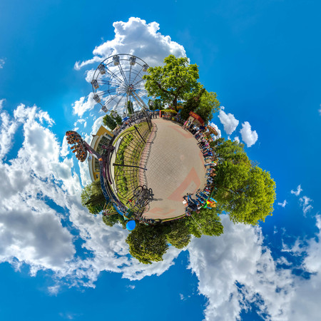 Green little planet with trees, white cluds and soft blue sky. Tiny planet of amusement park. 360 viewing angel.
