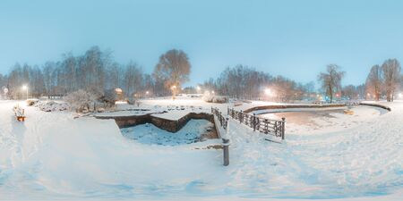 Image with 3D spherical panorama with 360 degree viewing angle. Snowy winter in park with trees at the evening. Burning lanterns. Full equirectangular projection. Ready for virtual reality in vr. Stock Photo