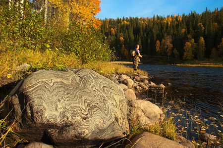 A big stone with beautiful pattern. Fisherman on background.