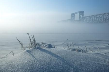 Winterlandschaft des nebeligen Morgens. Gefrorene Kräuter auf Vordergrund und Brücke auf Hintergrund. Standard-Bild - 76627764