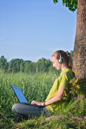 Teenage girl with headphones and computer at the country side photo