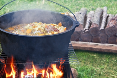 Kettle with food on campfire photo