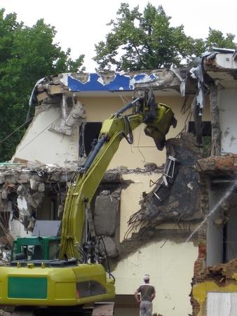 demolished: Demolition, construction. Crane dismantling building.
