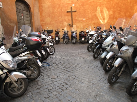 parked: Row of the motorcycles on the old street in Roma