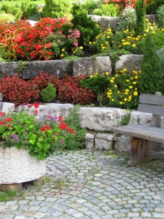 Stenen muur, bank en planten op kleurrijke aangelegde tuin