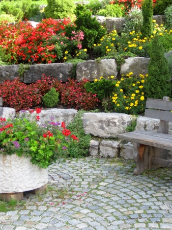 home garden: Stone wall, bench and plants on colorful landscaped garden