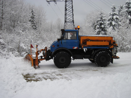 cleaning crew: Machinery with snowplough cleaning road by removing snow from intercity highway after winter blizzard