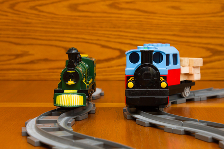 The toy train goes on rails. On a brown background Stock Photo
