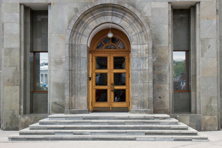 wooden doors in office building. Gray marble facade
