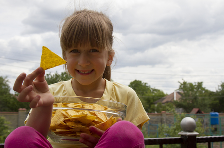 Little girl with chips in her hand