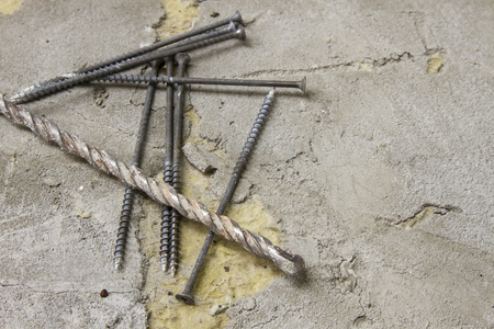 Old screws and a drill on a gray background