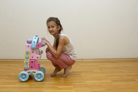 eight year old: Seven-year-old girl playing with toys in the room