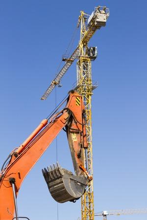 Orange excavator and tower crane against the blue sky 版權商用圖片