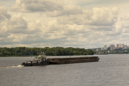 floating bridge: The old barge is floating along a wide river toned