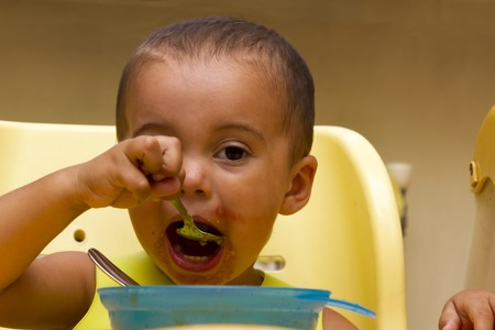 A Little b eating her dinner and making a mess Stock Photo