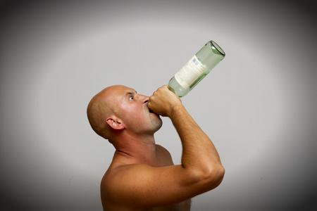 A drunkard drinks from a bottle